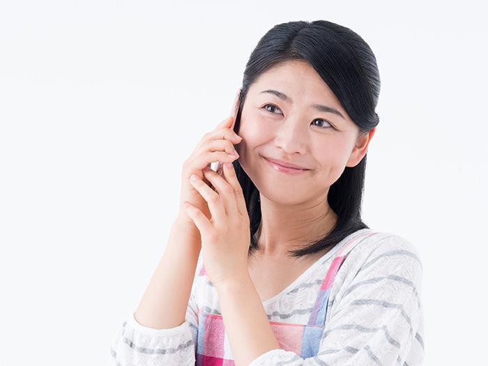 笑顔で電話をかける女性