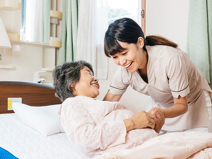 ベッドから起き上がる女性と補助するスタッフ