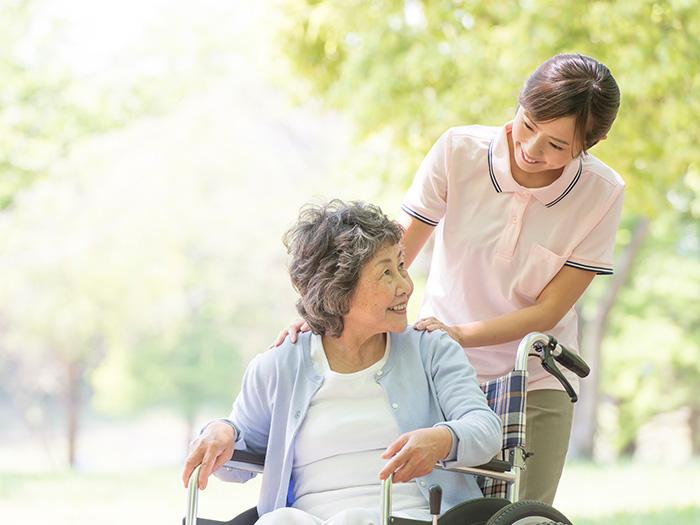 車椅子を押す女性スタッフ