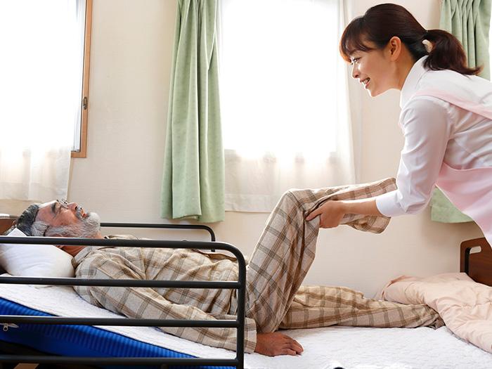 ベッドに横たわりリハビリ中のご利用者様とスタッフ