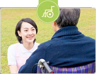 車椅子に乗る男性と会話する女性スタッフ