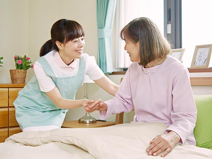 ベッドから起き上がる女性と笑顔のスタッフ